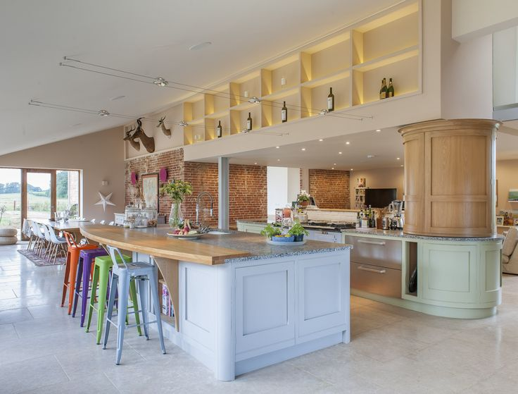 Brightly coloured stools complement the pale pastel colours in this bespoke hand painted Bryan Turner Kitchen. Unique use of striplights to draw attention to shelves: perfect for displaying your favourite bottle of bubbly