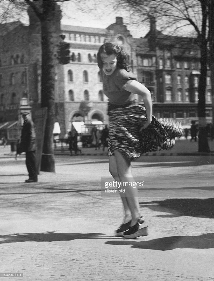 Women pictures Woman trying to prevent her skirt from being blown up by the wind - 1942 - Published by: 'Erika' August 1942 Vintage property of ullstein bild