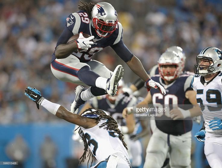 LeGarrette Blount #29 of the New England Patriots jumps over Tre Boston #33 of…