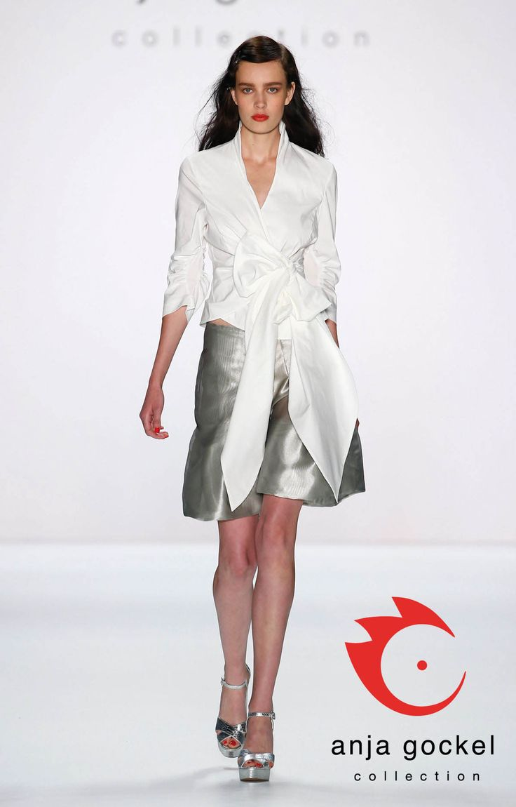 Feminine extravagance created by the teaming of a pure white wrap blouse and a shiny silver organza skirt. The oversized bow accentuates the waistline and creates a gorgeous, even silhouette. A must have for women who want to decrease wide shoulders!