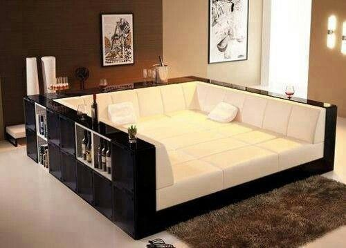 Living room. I was thinking you could make this yourself using a queen or king size bed, cheap bookshelves around it or even build a type of bed frame resembling this might be cheaper, then get that foam stuff for the edges, fit your desired fabric, some pillows to accent, and wallah!