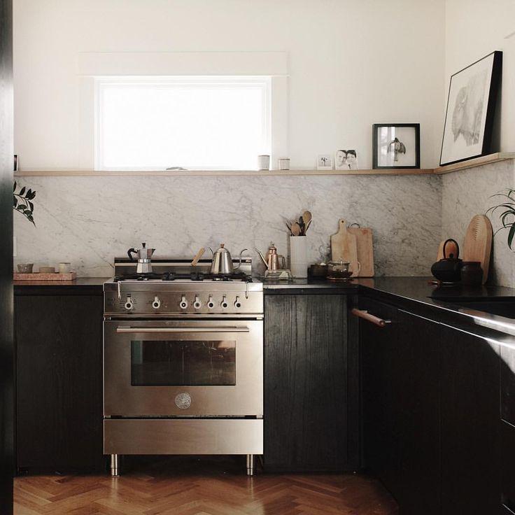 Kitchen remodel. Ebonized ash cabinetry. Honed absolute black granite countertop. Carrara marble backsplash. Bertazzoni range. Custom panel dishwasher. White oak herringbone floors.