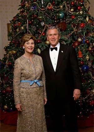 U.S. President George W. Bush and first lady Laura Bush stand in front of the official White House Christmas Tree during the 2004 holiday season in the Blue Room of the White House December 5, 2004 in Washington, DC.
