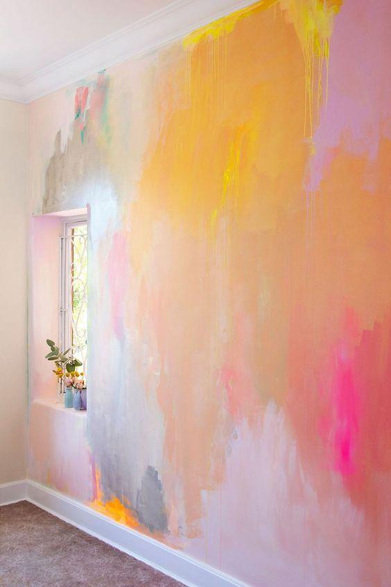 Helle, fröhlich gestaltete Schlafzimmeridee mit gemaltem abstraktem Wandgemälde in erdigen Sommerfarben wie Pfirsich, Koralle, Gelb und Pink, mit silbermetallischem …