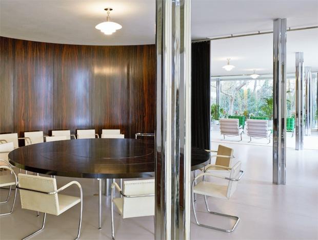 No salão principal, móveis de Mies, como as cadeiras Brno, e o painel de madeira de ébano de Makassar, um dos materiais mais luxuosos usados na decoração.