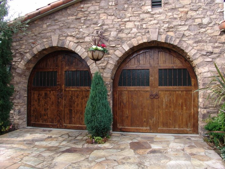 Mediterranean Garage With Rustic Doors Flagstone Driveway Stone Wall Siding And A Renaissance Revival Look The Arched Were Custom Made