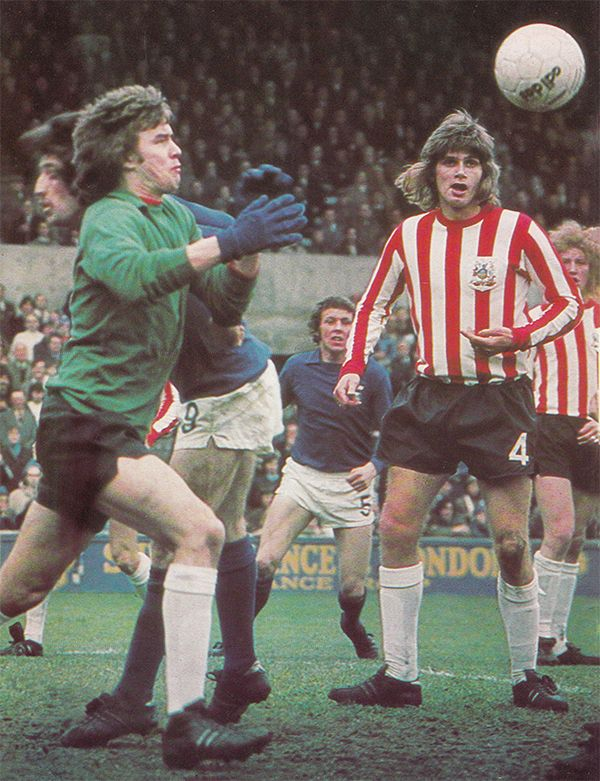 5th January 1974. Sheffield United goalkeeper Tom McAlister feeling the full force of Ipswich Town centre forward David Johnson in the FA Cup 3rd Round, at Portman Road.