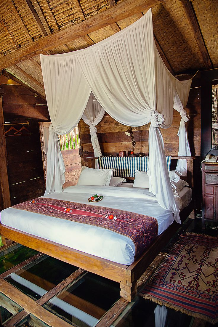 Part of the Bambu Inda Hotel in Bali, Udang House features a room with a glass-bottomed floor. The rustic suite is finished in teak and furniture includes lamps made from shrimp baskets