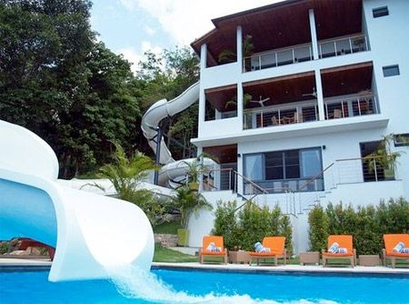 3 story house with a slide from the balcony