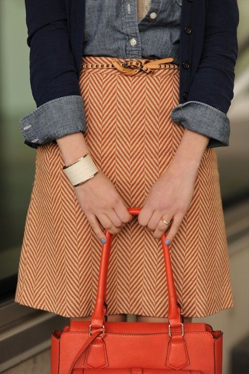 denim under navy cardigan, tweed herringbone skirt with skinny studded belt, wide cream cuff, and that gorgeous orange bag