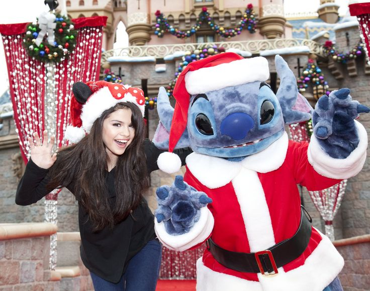 """In this handout image provided by Disney, Selena Gomez meets """"Santa"""" Stitch at Sleeping Beauty Winter Castle at Disneyland on November 7, 2009 in Anaheim, California. The meeting took place while taping a segment for the 2009 Disney Parks Christmas Day Parade airing December 25, 2009 on ABC ."""