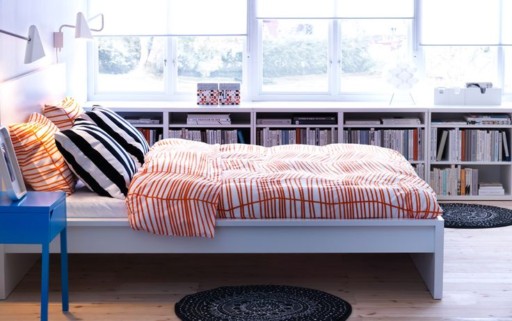 MALM white bed with SELJE blue bedside table and ÖDESTRÄD orange quilt cover and pillowcases  i like the low storage shelves under the window