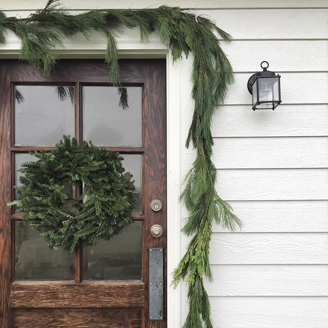 Farmhouse door wrapped in greenery and a wreath....a simple way to decorate for Christmas