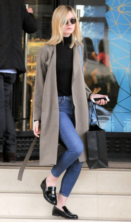Elle Fanning in skinny jeans, a black turtleneck, camel coat and loafers