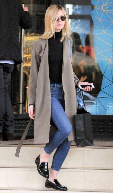 Elle Fanning in skinny jeans, a black turtleneck, camel coat and loafers