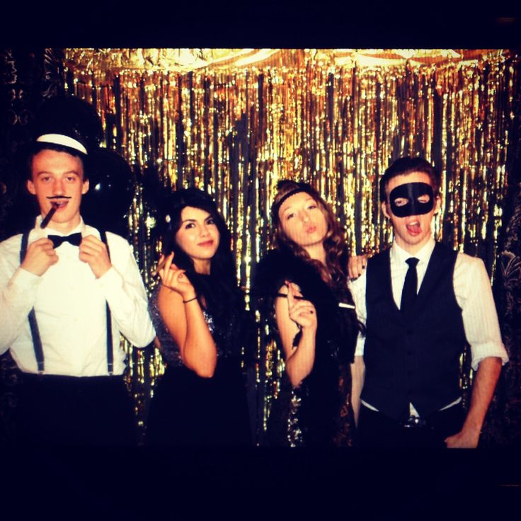 Black sheet, gold tinsel, black balloons. Great gatsby theme photo booth backdrop.