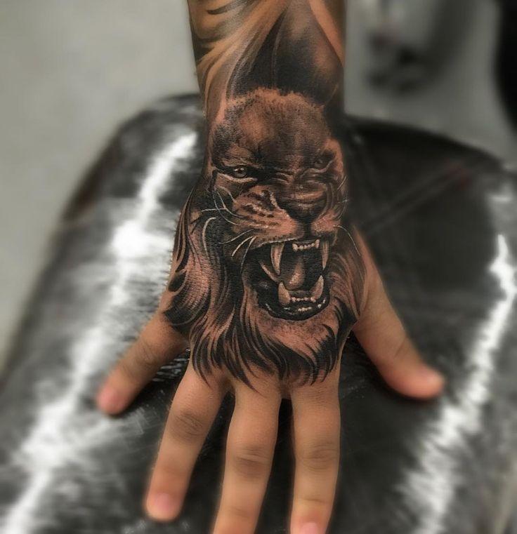 Roaring lion hand tattoo
