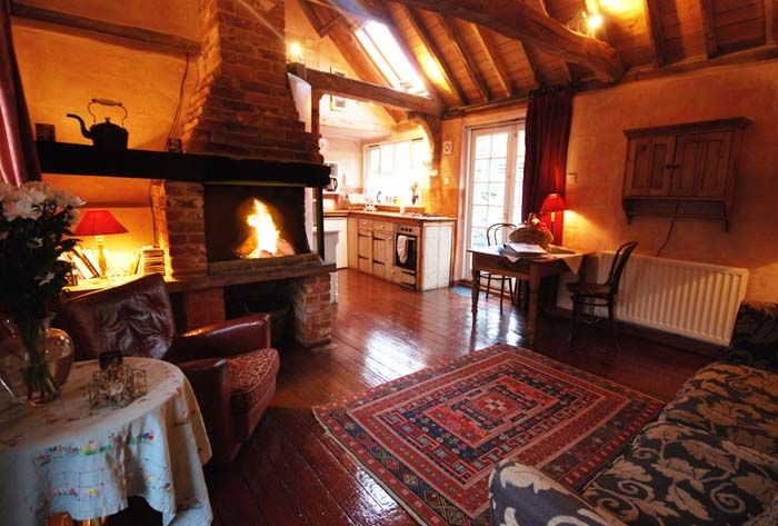 The cosy open lounge and kitchen area with a raised open fire. http://www.grove-cottages.co.uk/Rose%20Cottage/