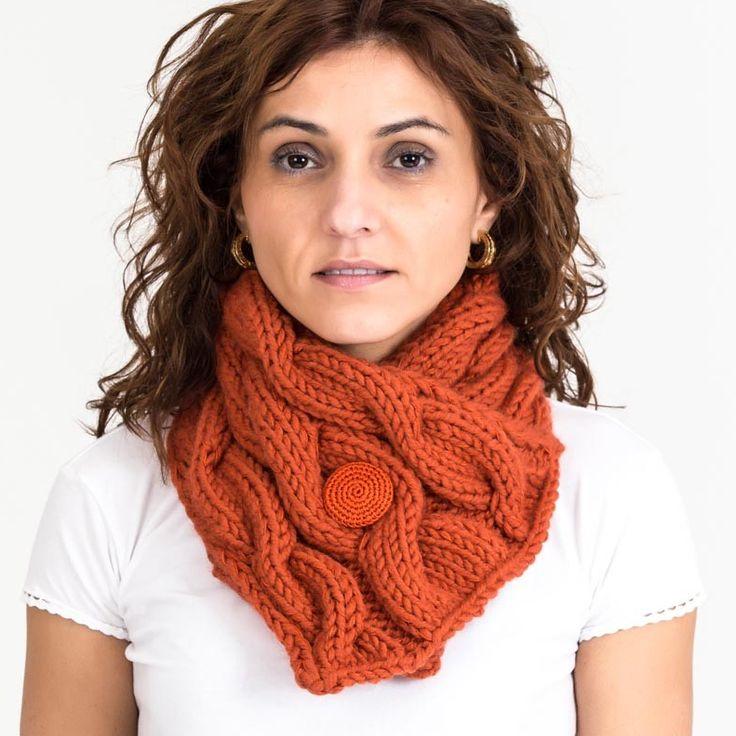 Bufanda elaborada artesanalmente con lana sintética e hilo perlé, cerrado con un botón forrado con técnica de crochet con hilo perlé. Se ha tejido en dos agujas un rectangulo con ambos hilos, formando en el  tejido ochos a todo lo largo