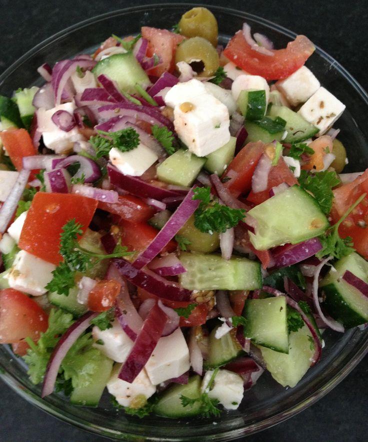 Griekse salade met feta, rode ui, komkommer, tomaat, olijven, peterselie, olijfolie, oregano, teentje knoflook en citroensap. Heerlijk.