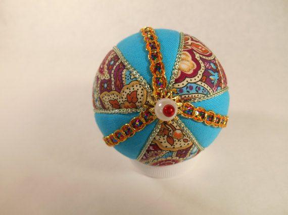 Questo ornamento è rivestito in tessuto aqua e multicolord, con cavo variegato di trim e color champagne. Condita con finte perle e perline di acrilico rossi. Il fondo è rifinito con una spilla di perla e con testa perlata finta. Palla è di circa 2-3/4 pollici alto. Ornamento è fatto utilizzando lo stile di giapponese chiamato Kimekomi che generalmente significa tuck. Un disegno è disegnato su una pallina di polistirolo, che viene tagliata con un coltello artigianale, quindi tessuto n...