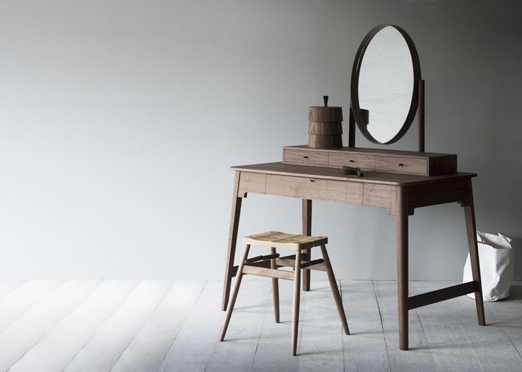 The Lana dressing table's lower lockable drawer houses a removable leather lined jewellery tray, and a drawer divider. The surface box consists of 3 smaller drawer sections and the dressing table comes with a stack of 3 round solid walnut storage boxes with a single lid and bristle handle. The dressing table also features a hidden drawer and a cheval mirror.