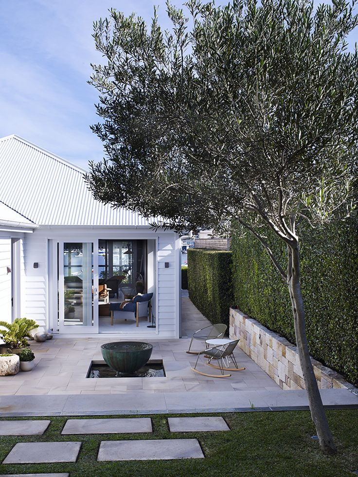 The clean stone wall, geometrically spaced concrete pavers in grass, mod rockers, and every detail on the house... Love