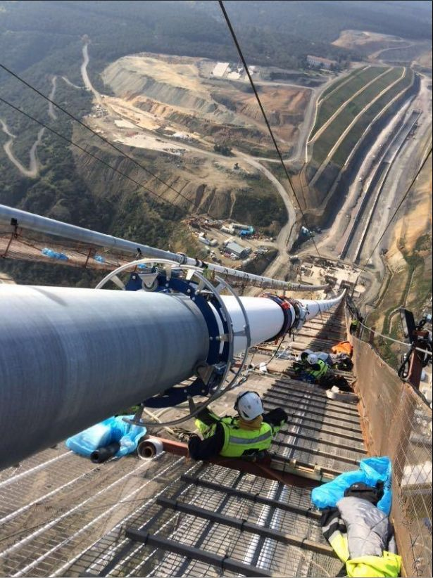 Wrapping the main cables of a suspension bridge. You can see the two main cables going into anchors in bedrock. Yavuz Sultan Selim Bridge in Turkey.