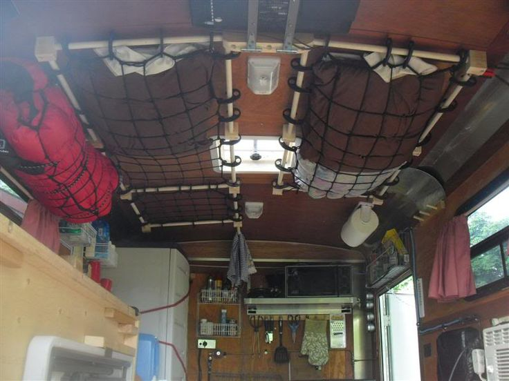 Two cargo nets are attached to a tiny trailer's ceiling and storing clothes.