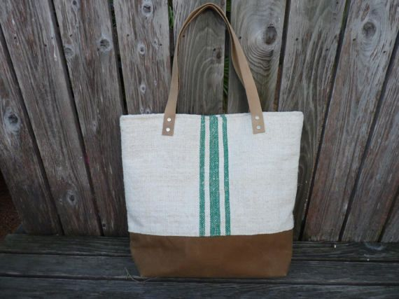 Authentic heavy weight, light oatmeal colored linen antique European grain sack with 3 vertical green stripes is repurposed into this unique, sturdy tote bag. It features a dark tan waxed canvas bottom and light tan leather straps. The interior lining is make from cream colored cotton twill with a 3 sectioned, vintage mid century floral print bark cloth pocket. The top is secured with a magnetic snap.  It measures a generous 18 in. wide, 15 in. high, and 5 in. deep. The strap drop measures…