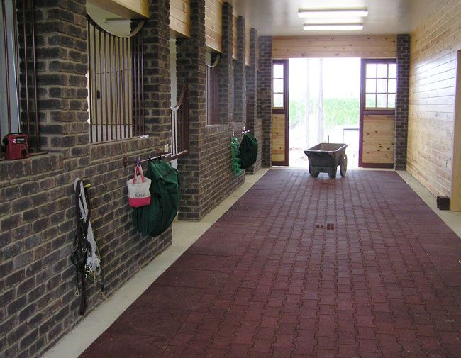 Interlocking re-cycled rubber pavers.  Take a look at those brick stalls while you're at it.