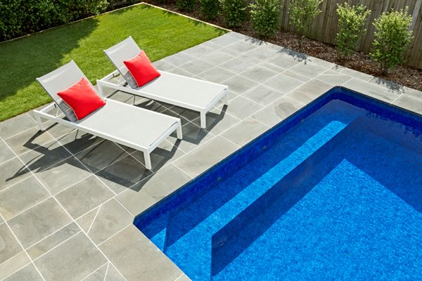 This Albatross Pool features a purpose built comfort seat spanning the width of the pool and measures 7.0m x 4.0m. Complete with synthetic grass, bluestone, lounge chairs and splashes of red, this stunning pool is located in Burwood East, Melbourne.