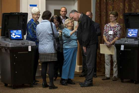 Minerva Turpin, 99, talked with Senator Tim Kaine after he and his wife, Anne Holton, left, voted at... - Ruth Fremson/The New York Times