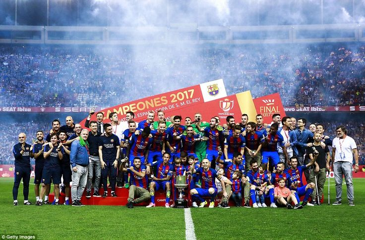 Barcelona's players and staff pose for a photo with their newly earned Copa del Rey after winning the game in Madrid