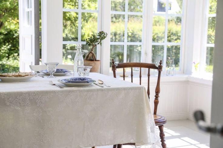 Husets nedre plan disponeras med vardagsrum, kök, sovrum, glasveranda och badrum. I det stora och lättmöblerade vardagsrummet är det öppet upp till nock, och de vackra takbjälkarna skapar en fantastisk atmosfär. Ljuset strömmar in, och när skymningen väl fallit är det mysigt att elda i braskaminen. Pardörrar leder ut till en fin uteplats. Liksom i övriga huset är väggarna klädda med panel respektive tapet i traditionellt mönster och golvens vackra furutiljor har lutats och såpats.
