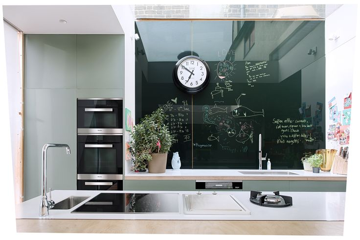 Professional chef Anna Hansen, MBE features a unique splashback design to compliment the olive green cupboards. Integrated appliances have been placed for ease of use, and create a central cooking point in the kitchen