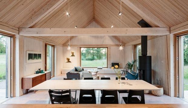 Dit houten huis middenin een ruw landschap en aan een klein meertje laat je helemaal tot rust komen. Met een grote open ruimte lijkt het huis nog groter.