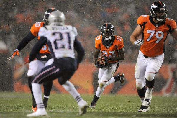 Running back Ronnie Hillman #23 of the Denver Broncos scores a second quarter touchdown against cornerback Malcolm Butler #21 of the New England Patriots at Sports Authority Field at Mile High on November 29, 2015 in Denver, Colorado.