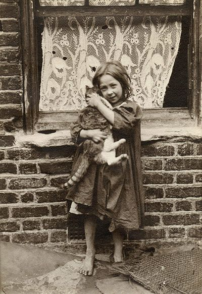 """Amazing shots of East End street kids in Victorian London. A young girl cuddles with a cat. Horace Warner took these pictures of the children he called """"Spitalfields nippers"""", each one as bursting with character as the last."""