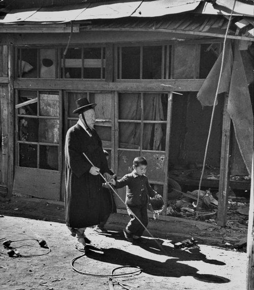 A boy leads an old blind man through war-torn streets, past damaged storefronts. Korea, 1951.  John Dominis