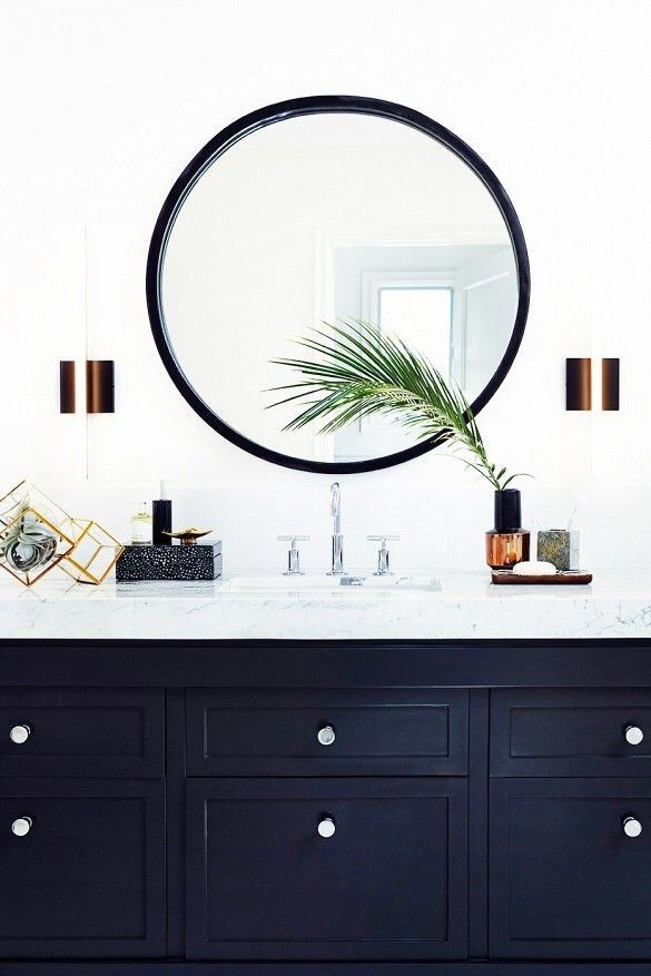 This navy blue bathroom vanity and white marble counter top is accentuated with a steel-framed round mirror and copper sconces.