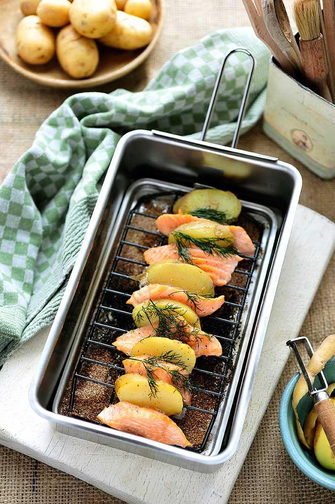 Bereiden: Stoom de aardappelen beetgaar, laat wat afkoelen. Snij de zalm in plakjes van 1 cm dik. Snij de aardappelen in plakjes. Strooi een laagje zaagsel op de bodem van de rookdoos. Strijk het rooster in met olie en plaats het in de doos. Leg er afwisselend een plak aardappel en een plakje zalm op.