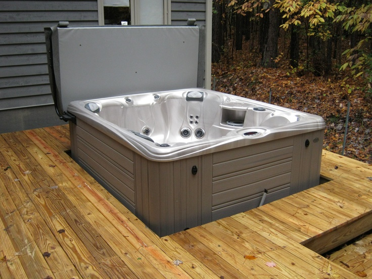 caldera martinique hot tub in a new deck with a coverlifter from atlantic spas and billiards this hot spring grandee is tucked into a beautiful pergola and