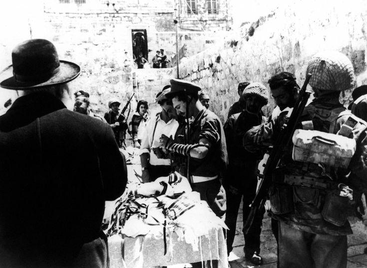 Un judío ortodoxo presta prendas de oración y filacterias para que los soldados israelíes recen en el Muro de las Lamentaciones de Jerusalén, el 8 de junio de 1967, en la Guerra de los Seis Días.