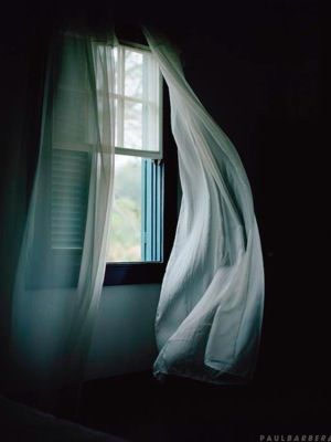 What lies within the dimness of the room?