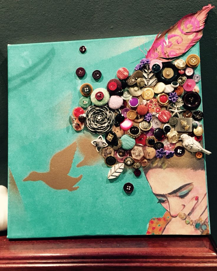 Frida inspired canvas with antique and plastic buttons, painted pigeon feather and gold spray