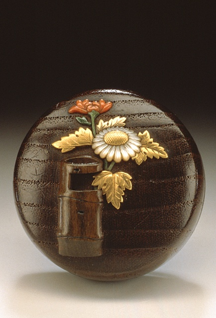 Japan Chrysanthemum in Flower Vessel, late 19th century Netsuke, Wood with gold, coral, mother-of-pearl, metal inlays; manju type