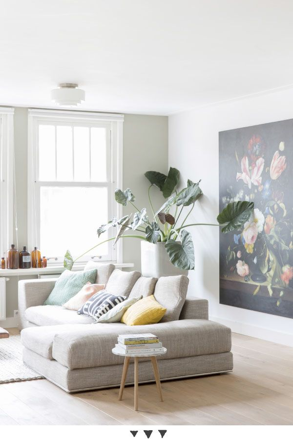 That's the dream living room! L shaped sofa with cosy scatter cushions, massive pot plant and a big painting on the wall