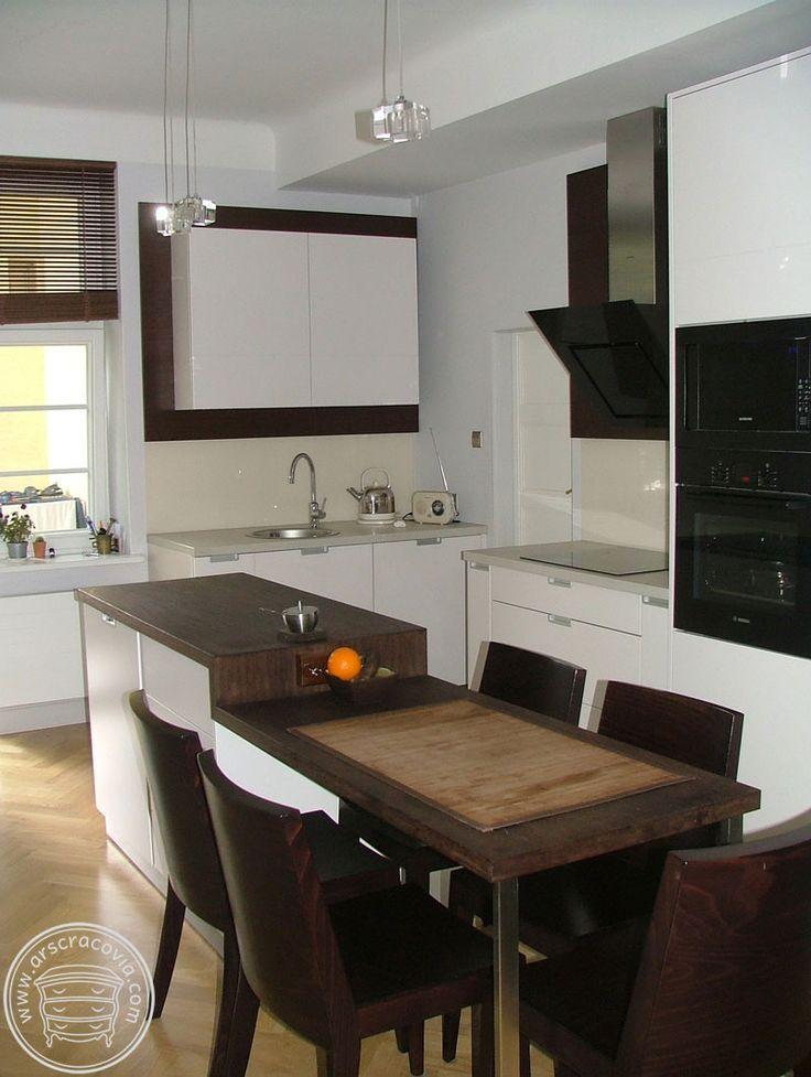 Kuchnia z wyspą, elementy drewniane to naturalne, olejowane drewno wenge, blaty robocze pokryte laminatem HPL, fronty- malowany mdf, ściana-szkło lakierowane.