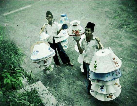 Penjual kap lampu di jalan dengan pikolans (carry stick) di Surabaja pada tahun 1950 Lampenkapverkopers op straat met pikolans (draagstok) in Surabaja 1950. Wiwien Lasito saved to Sejarah Soerabaia-Pinterest